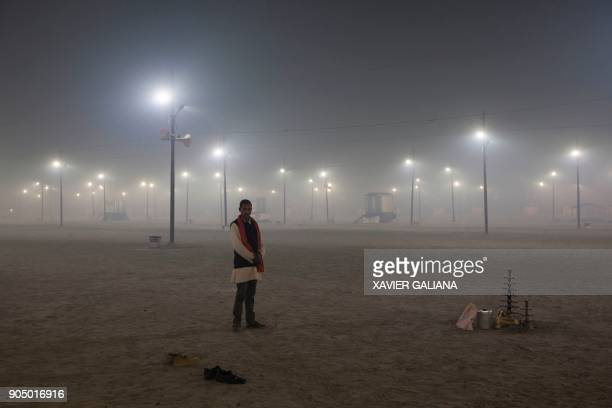 TOPSHOT In this photograph taken on January 14 2018 an Indian devotee stands at Sangam the confluence of the rivers Ganges Yamuna and mythical...