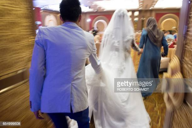 In this photograph taken on January 15 a bride is escorted into a wedding hall on her wedding day at the Al Meroz hotel in Bangkok From hotels with...