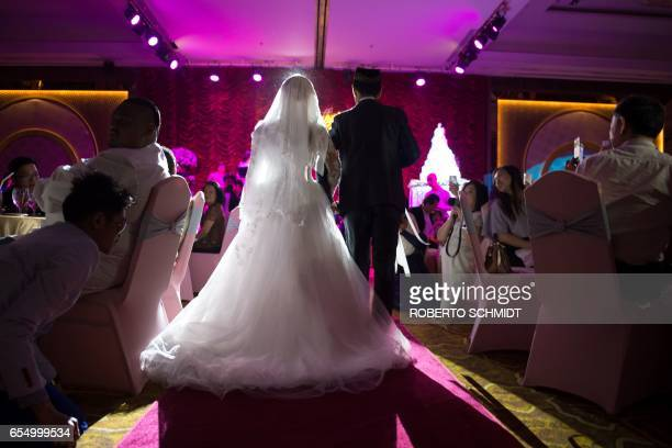 In this photograph taken on January 15 a newly married couple enter a wedding hall during their wedding reception at the Al Meroz hotel in Bangkok...