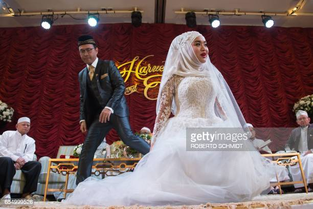 In this photograph taken on January 15 a newly married woman and her husband get ready to pose for a portrait during their wedding reception at the...