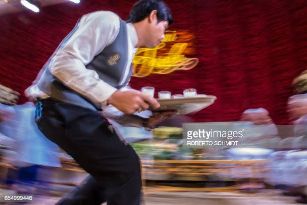 In this photograph taken on January 15 a waiter carries nonalcoholic beverages during a wedding reception at the Al Meroz hotel in Bangkok From...