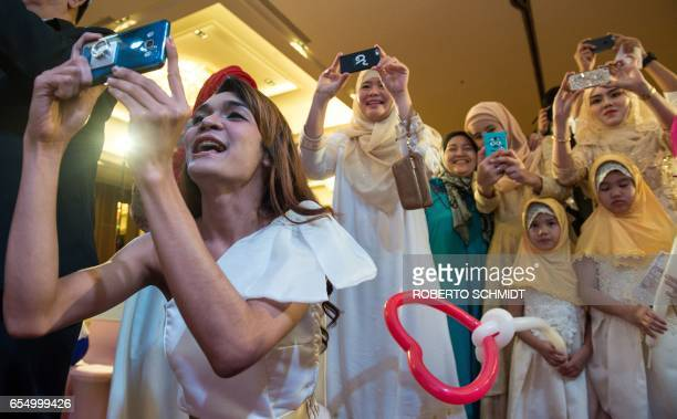 In this photograph taken on January 15 guests and family members of a newlywed couple take photos of them during a wedding reception at Al Meroz...