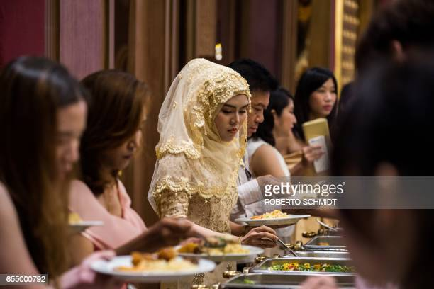 In this photograph taken on January 15 guests choose food items during a wedding reception at the Al Meroz hotel in Bangkok From hotels with...