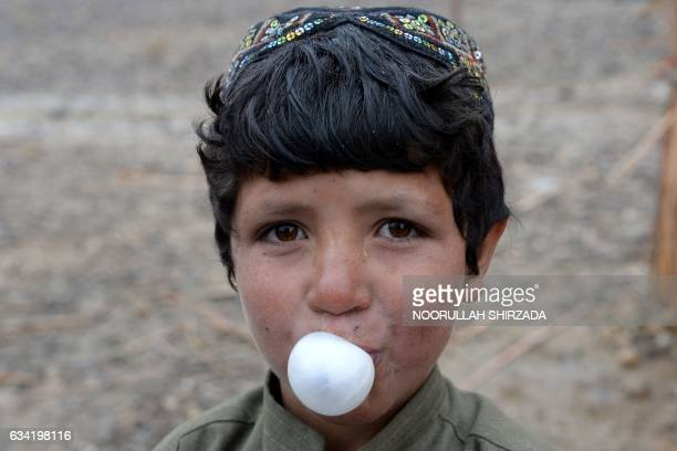 In this photograph taken on January 18 an Afghan child blows a bubble with chewing gum as he stands outside a mud house at a refugee camp on the...
