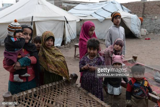 In this photograph taken on January 18 internally displaced children gather near their tent on the outskirts of Jalalabad Marooned in a tent...