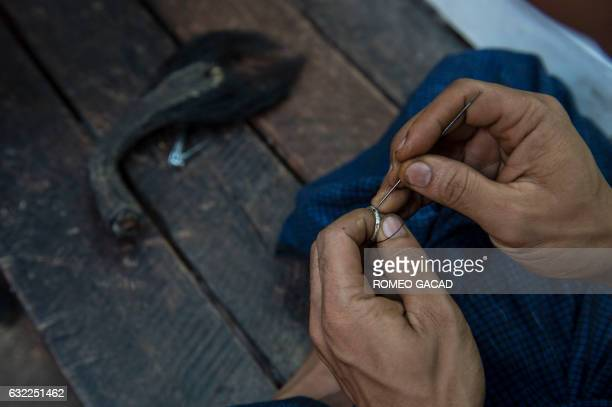 In this photograph taken on January 19 a vendor insert an elephant hair on a ring cut from an portion of an elephants's tail seen at left for sale at...
