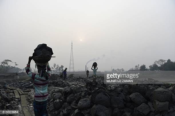In this photograph taken on January 19 Bangladeshi labourers carry loads of clay for bricks as they work at a brick factory on the outskirts of...