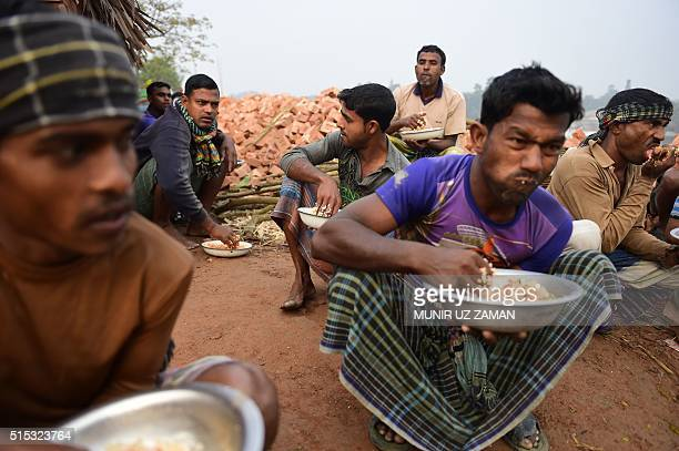 In this photograph taken on January 19 Bangladeshi labourers eat breakfast during a break from work at a brick factory on the outskirts of Khulna...