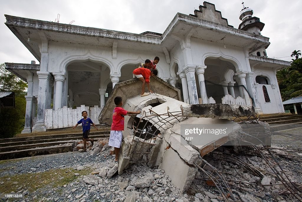 In this photograph taken on January 22, 2012 children play on a toppled mosque minaret in Pidie located in Indonesia's Aceh province following a 5.9-magnitude earthquake that struck off Aceh province early on January 22, killing an eight-year old girl and injuring seven others, officials said, as panicked residents rushed outdoors. The quake struck 112 kilometres (70 miles) southeast of provincial capital of Banda Aceh at 22:22 GMT at a depth of 37 kilometres, the US Geological Survey said.