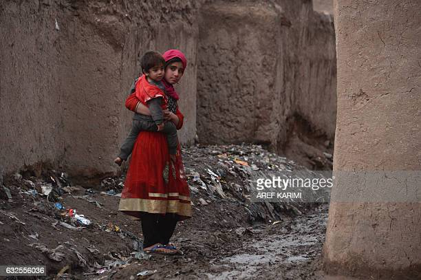 TOPSHOT In this photograph taken on January 23 an Afghan girl holds her brother as she walks through a refugee camp in Herat / AFP / AREF KARIMI