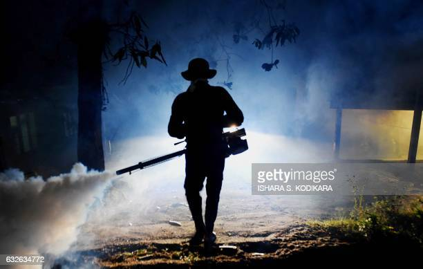 TOPSHOT In this photograph taken on January 24 a Sri Lankan health worker sprays a neighbourhood with a fog used to ward off mosquitos in Biyagama on...