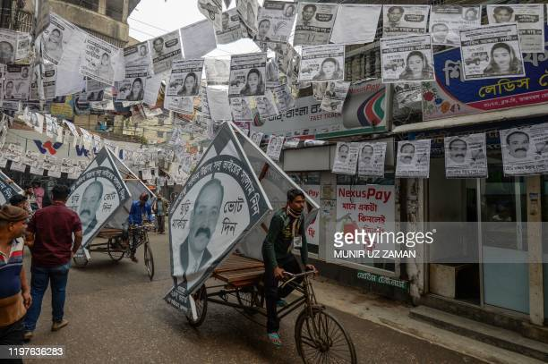 In this photograph taken on January 29 a threewheeler cart driver carries a portrait of an election candidate on a street adorned with election...