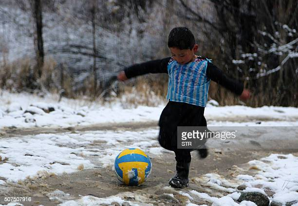 TOPSHOT In this photograph taken on January 29 Afghan boy and Lionel Messi fan Murtaza Ahmadi wears a plastic bag jersey as he plays football in...