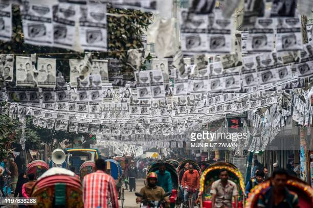 In this photograph taken on January 29 commuters make their way on a street adorned with election posters laminated with plastic in Dhaka  Dhaka is...