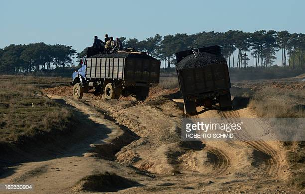 In this photograph taken on January 29 men ride the back of a charcoal ladden truck through fields dotted with private mine shafts near Mulang...