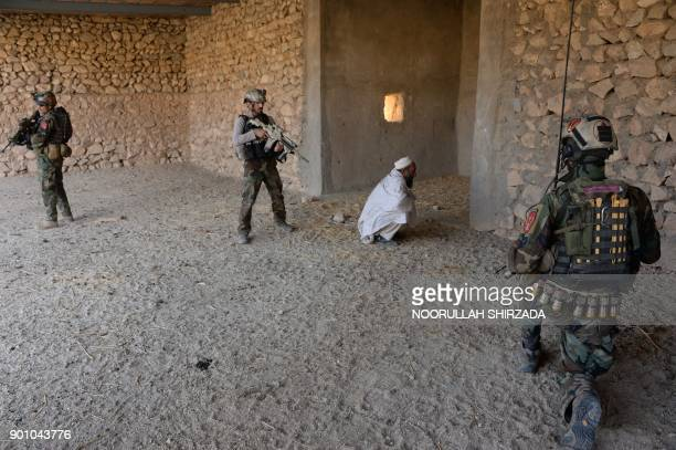 In this photograph taken on January 3 Afghan commandos forces arrest a suspected man during ongoing USAfghan military operation against Islamic State...