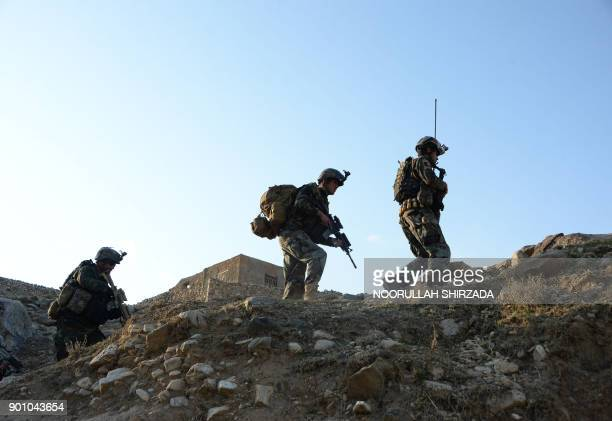 In this photograph taken on January 3 Afghan commandos forces patrol during ongoing US-Afghan military operation against Islamic State militants in...
