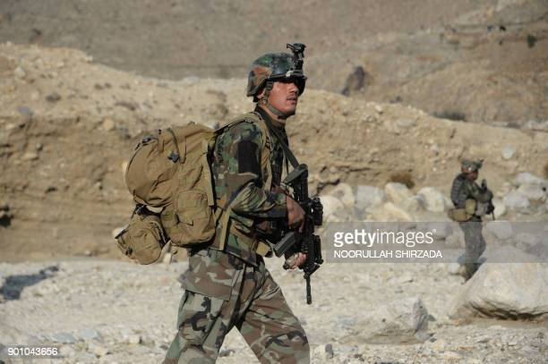 In this photograph taken on January 3 Afghan commandos forces patrol during ongoing USAfghan military operation against Islamic State militants in...