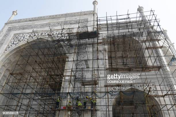 In this photograph taken on January 3 Indian labourers work amid scaffolding during conservation work at the Taj Mahal in Agra. - Restoration work at...