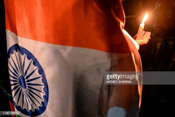 In this photograph taken on January 7 a protester wraps himself with an Indian national flag as he holds a candle during a demonstration at Shaheen...