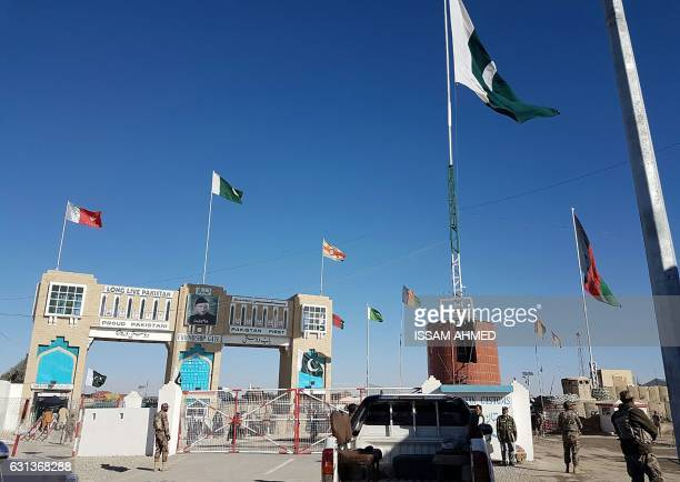 In this photograph taken on January 7 Pakistan security personnel look on as travellers wait to cross the border between Pakistan and Afghanistan at...
