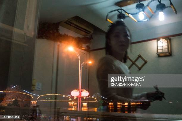 In this photograph taken on January 8 a reflection of a North Korean waitress is seen inside the Song Tao Garden restaurant as the lights are seen on...