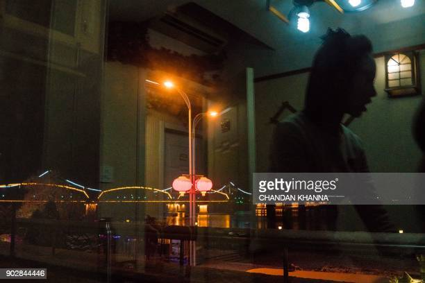 TOPSHOT In this photograph taken on January 8 a reflection of a North Korean waitress is seen inside the Song Tao Garden restaurant as the lights are...