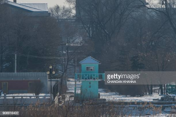 In this photograph taken on January 9 2018 a North Korean soldier is seen sitting inside a guard post on the bank of the Yalu river near the North...