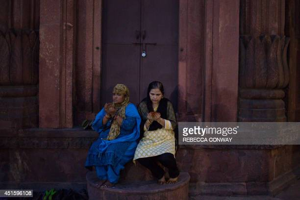 In this photograph taken on July 1 2014 two Indian muslim women pray in the courtyard of the Jama Masjid mosque in New Delhi as they get ready to...