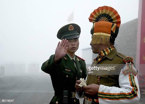 In this photograph taken on July 10 A Chinese soldier gestures as he stands near an Indian soldier on the Chinese side of the ancient Nathu La border...