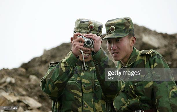 In this photograph taken on July 10 a Chinese soldier watches the screen on his comrade's digital camera as they stand guard on the Chinese side of...