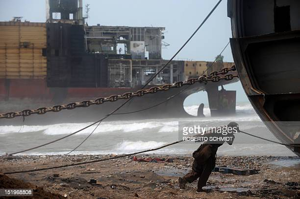In this photograph taken on July 10 a Pakistani shipyard worker pulls on a wire attached to a motor that will help peel away part of the outer...