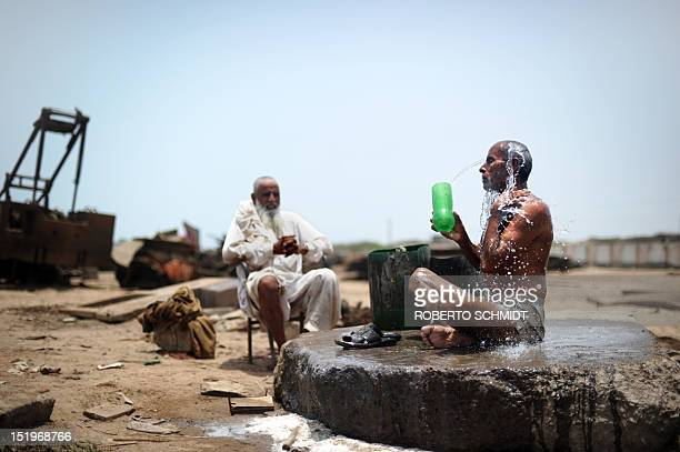 In this photograph taken on July 10 a shipyard worker washes himself at the end of his shift next to one of the 127 shipbreaking plots in Geddani...