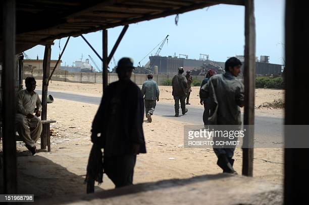 In this photograph taken on July 10 Pakistani workers leave a modest food kiosk after their lunch break near one of the 127 shipbreaking plots in...