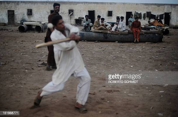 In this photograph taken on July 10 shipyard workers play cricket with a piece of wood and a plastic ball at the end of the day near rooms they rent...