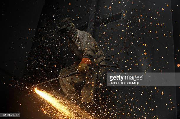 In this photograph taken on July 11 a Pakistani shipyard worker uses a blow torch to cut through metal inside the hull of a vessel beached at one of...