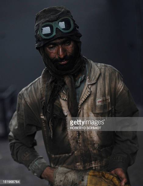 In this photograph taken on July 11 a shipyard worker end his shift cutting through metal inside the hull of a cargo ship being dismantled at one of...