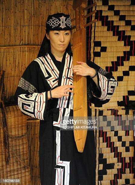 In this photograph taken on July 11 Japan's indigenous Aibu woman plays a harp at Nibutani Ainu Suseum at Biratori in Japan's northern island of...