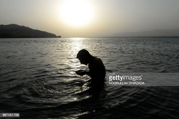 In this photograph taken on July 12 an Afghan man performs ablution before prayer in a river during sunset in Jalalabad.