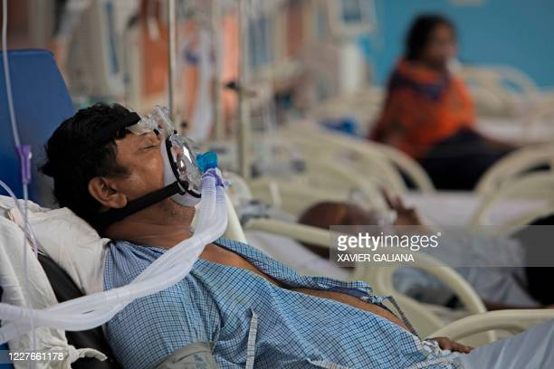 In this photograph taken on July 15 2020 a COVID19 coronavirus patient lies on a bed at the Intensive Care Unit of the Sharda Hospital in Greater...