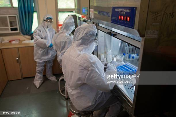 In this photograph taken on July 15 laboratory technicians wearing Personal Protective Equipment suits prepare samples to test for the COVID19...