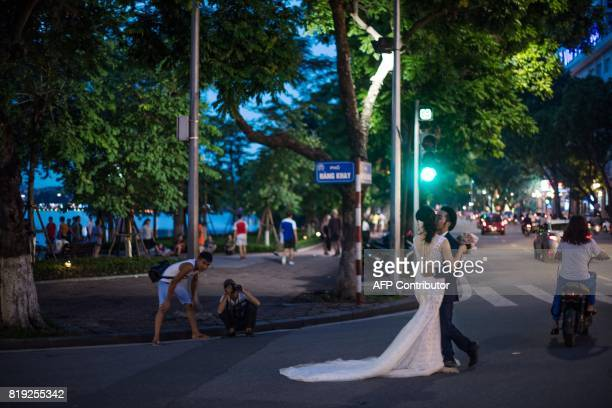 TOPSHOT In this photograph taken on July 19 a bride and groom get their photo taken by a portrait photographer in the streets of downtown Hanoi / AFP...