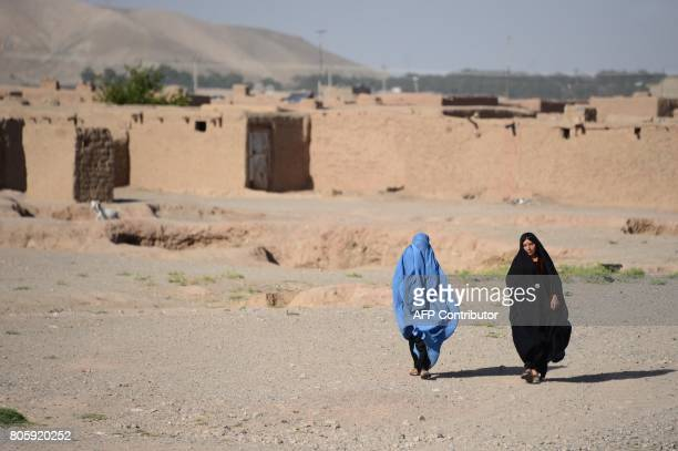 In this photograph taken on July 2 2017 internally displaced Afghan women walk on the outskirts of Herat / AFP PHOTO / HOSHANG HASHIMI