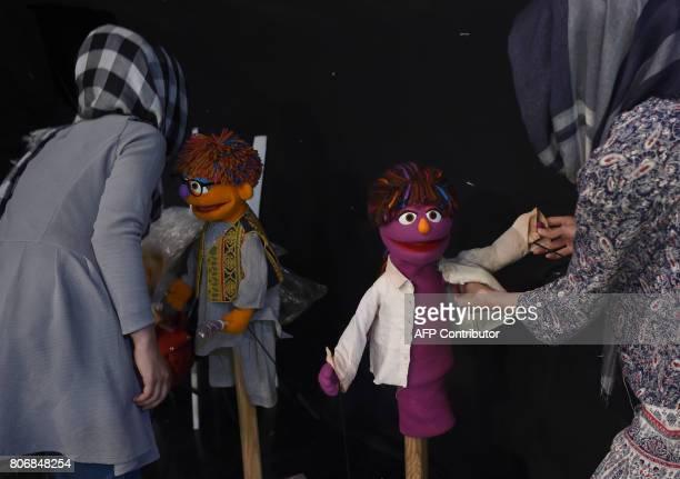 In this photograph taken on July 2 Afghan puppeteers Raziya Nazaria and Mansoora Shirzad dress Sesame Street Muppets 'Zeerak' and 'Zari' ahead of...