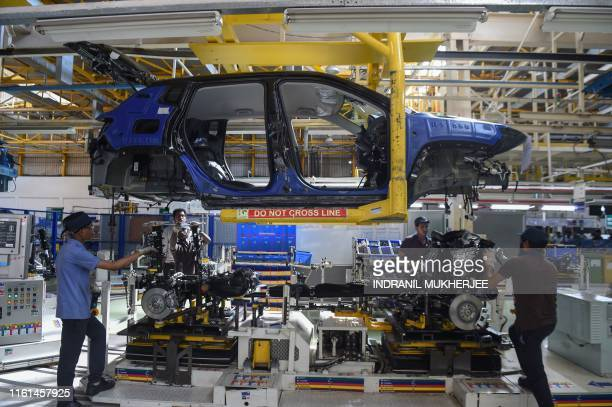 In this photograph taken on July 23 2019 workers assemble a car at a FCA India Automobiles manufacturing facility in Ranjangaon some 200km east of...