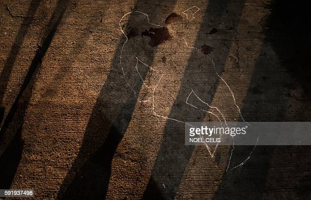 In this photograph taken on July 23 a chalk outline remains on a street in Manila after the funeral personnel moved the body of an unidentified man...