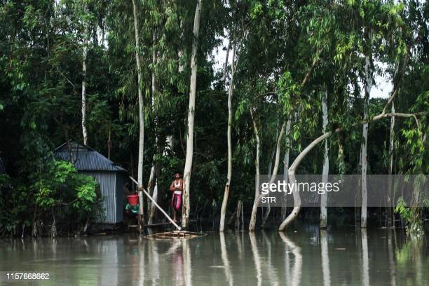 TOPSHOT In this photograph taken on July 25 a resident stands platform near a house in a flood afected area following monsoon rain in Kurigram...