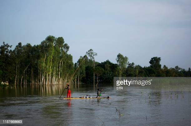 In this photograph taken on July 25 residents travel on a makeshift raft to collect drinking water in a flood afected area following monsoon rain in...