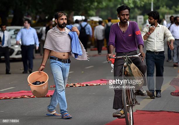 In this photograph taken on July 26 34 year old Indian man Santosh Singh walks with a bucket as he prepares to take a bath at his protest site at...