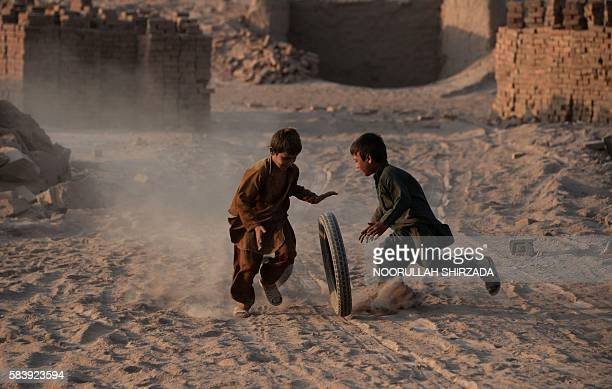 In this photograph taken on July 27 Afghan children play with a tyre along a dusty road on the outskirts of Jalalabad. / AFP / NOORULLAH SHIRZADA
